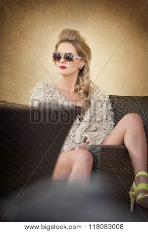 Attractive and sexy blonde woman with sunglasses posing provocatively sitting on chair