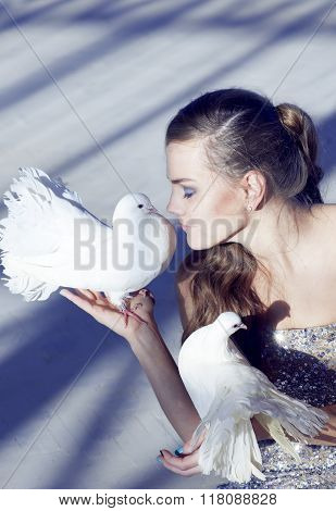 Gentle Portrait Of A Beautiful Girl With A White Dove, Over  A Shaded Blue Background.
