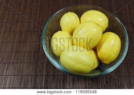Pile of fresh lemons in glass bowl
