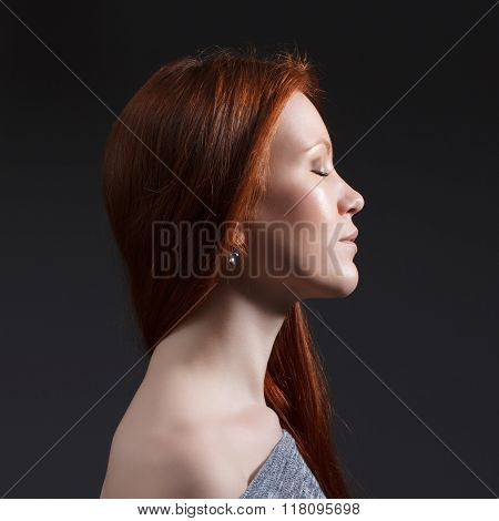 woman with red long hair in profile.