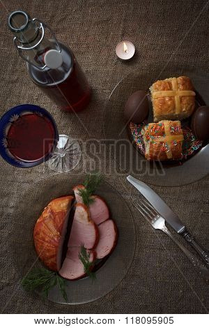 Easter Dinner Served On Burlap Tablecloth. Meat, Hot Cross Buns, Chocolate Eggs
