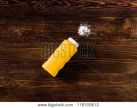 Spilled baby talcum powder on dark wooden background. Flat lay