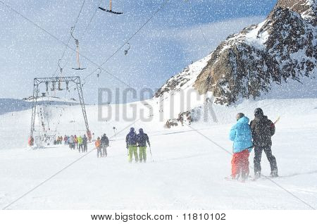 T Bar Ski Lift Pulling Couple Skiers Up The Slope. Snowy Winter In European Alps.
