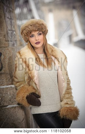 Attractive woman with brown fur cap and jacket enjoying the winter. Side view of fashionable blonde