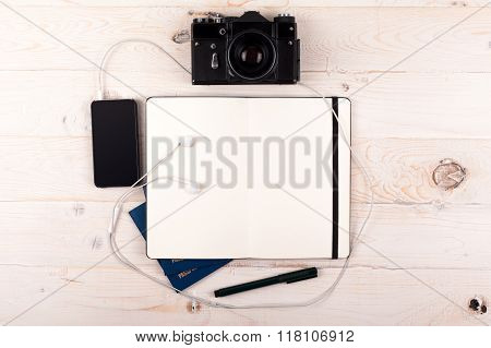 Outfit of traveler on a white wooden background