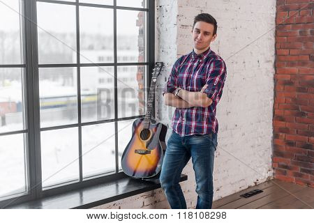 Handsome casual style man with guitar smiling and looking at camera.