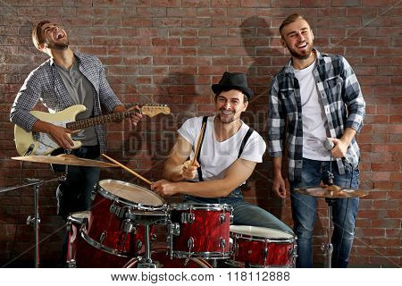 Musicians playing the drums on brick wall background