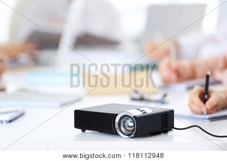Black projector on white table for business presentation in the foreground