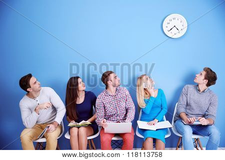 Young people sitting on a chairs and looking at the clock in blue hall