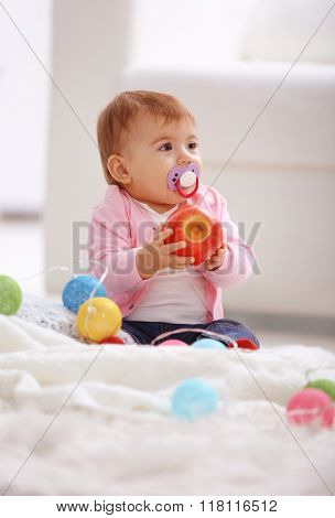 Sweet baby girl with a soother and apple sitting on floor