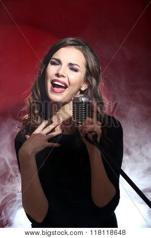 Attractive singing woman in white dense smoke on red background, close up