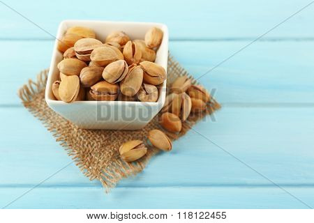Pistachios in the bowl on blue wooden background