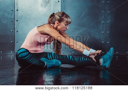 Fit woman doing stretching exercises her muscles back and legs before a training warm up at gym conc