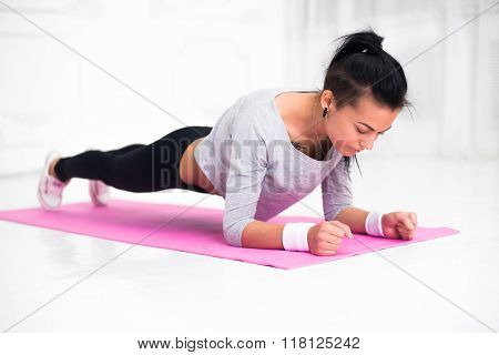 sporty fit sliming girl doing plank exercise in yoga class. fitness, home and diet concept.