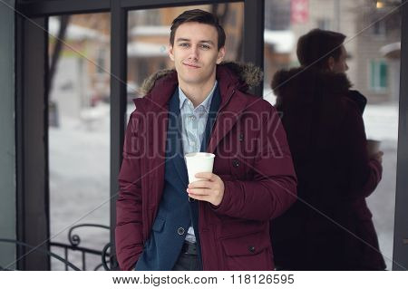 Young man in suit and unzipped coat drinking coffee on the street winter