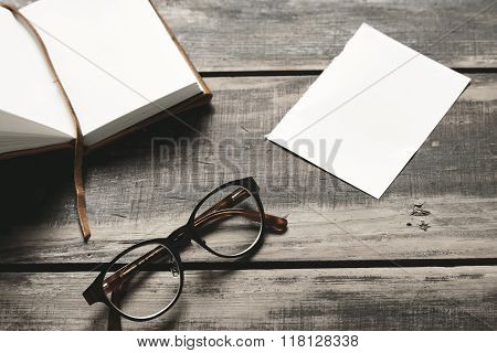 Opened Notebook, Glasses, Paper Sheet On Black Table