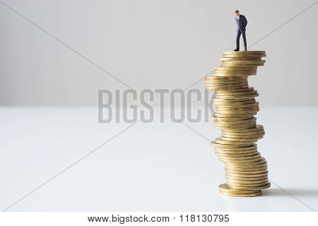 Businessman Standing On Risky Coin Stack.