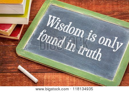 Wisdom is only found in truth - inspirational phrase on a slate blackboard with a white chalk and a stack of books against rustic wooden table