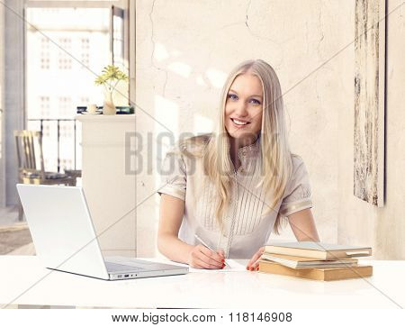 Attractive happy blonde casual caucasian woman studying at vintage home. Smiling, sitting at table with laptop computer, books and paper, writing, looking at camera.