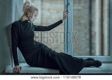 Woman Lying On The Window Sill And Sad.
