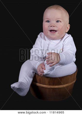das Kind sitzt in ein hölzerner Eimer