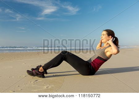 Shoot of a beautiful woman working her ABS in the beach