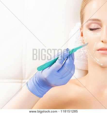 Beautiful girl with a drawing arrows over her face and a doctor hand with a scalpel. Aging and plastic surgery concept.