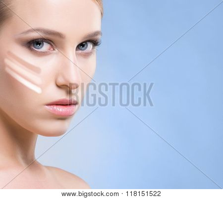Woman with a foundation cream on her face. Different tones. Makeup concept.