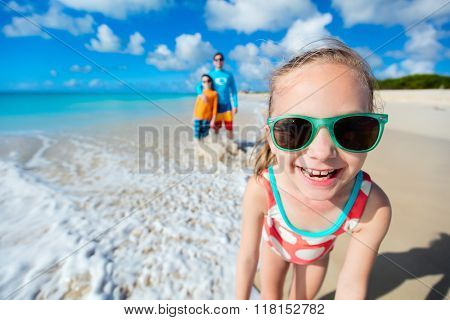 Little girl and her family father and brother enjoying beach vacation in Caribbean