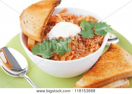red tomato soup with toasts on green plate
