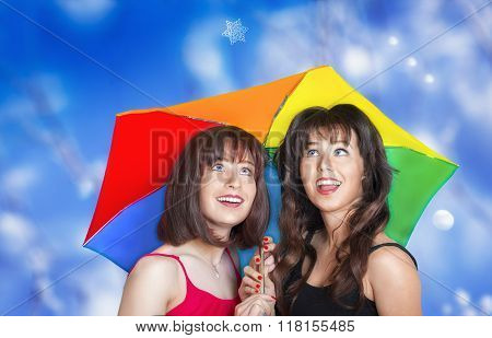 Two Smiling Girls Looking At The Snowflake Falling