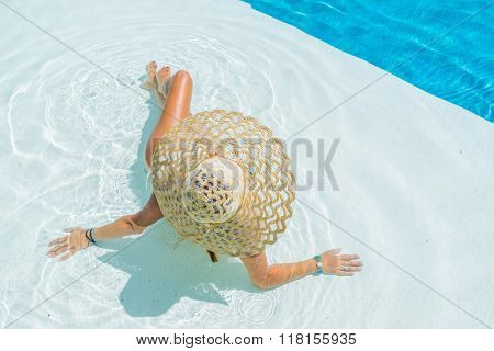 Woman on vacation relaxing by the swimming pool