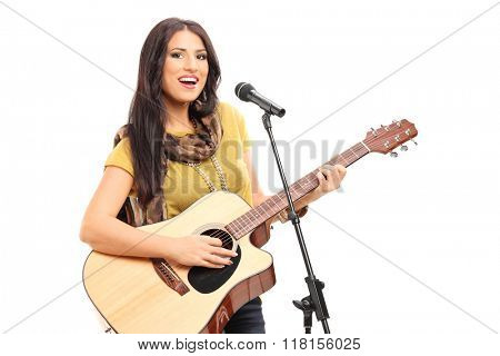 Female signer playing on acoustic guitar and singing on a microphone isolated on white background