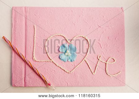 Notebooks greeting love pink on white table.
