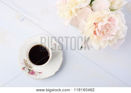 Still life with cup of coffee and flowers (peonies) on light  lilac wooden table.