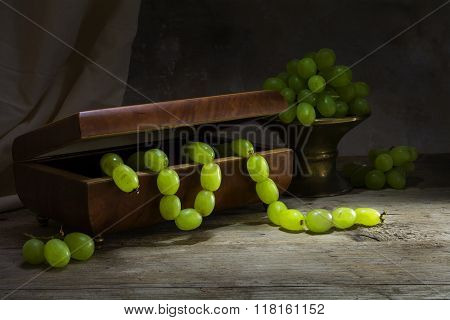 Green Grapes Hanging Like A Necklace From A Jewelery Box On A Rustic Wooden Table, Still Life Concep