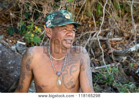 BAMBOO ISLAND, THAILAND - CIRCA FEBRUARY, 2015: Portrait of a Thai man with a tattoo on a background of tropical vegetation.