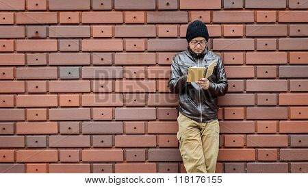 An Asian Man in a Brown Jacket with a Small Notebook