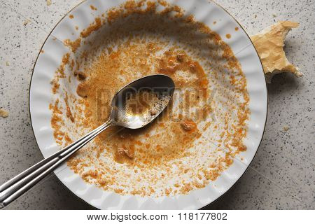 finished meal on a dirty plate with a spoon