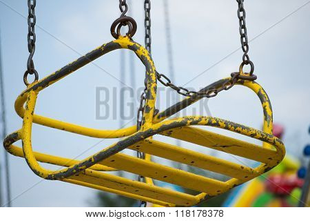 Yellow seat suspended on chains