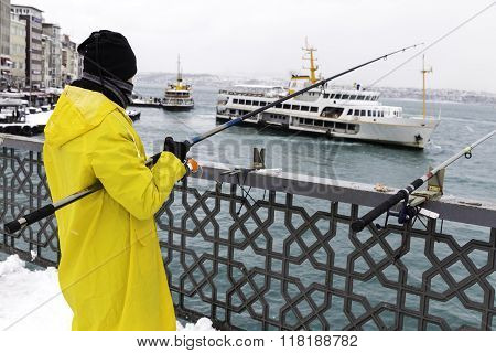 Unidentified Local Fishermen Wearing Yellow Raincoat Fishing On The Galata Bridge