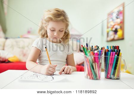 Portrait of child blonde girl drawing at home in her room