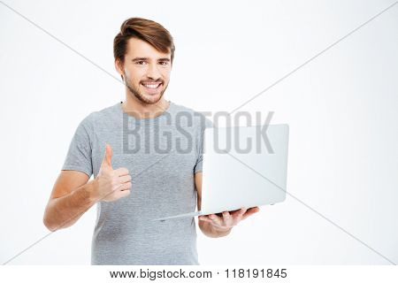 Smiling casual man holding laptop computer and showing thumb up isolated on a white background