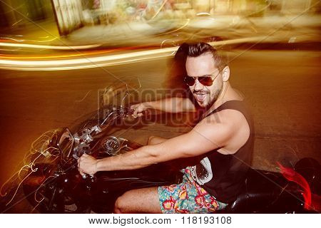 Long exposure portrait of hispanic yong man wearing sunglasses riding a motorcycle in night without helmet. High speed driving. Side view.