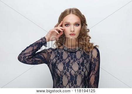 Young adorable blonde woman in blue dress with curly hairstyle touching her cheekbone posing on whit