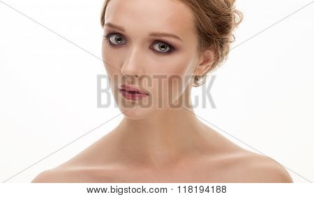 Closeup portrait of young shy cute blonde woman with trendy nude makeup posing with bare shoulders o