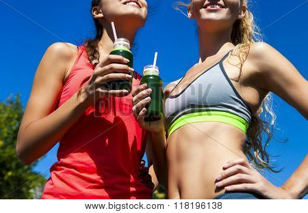 Two Happy Women Drinking Vegetable Smoothie After Fitness Running Workout