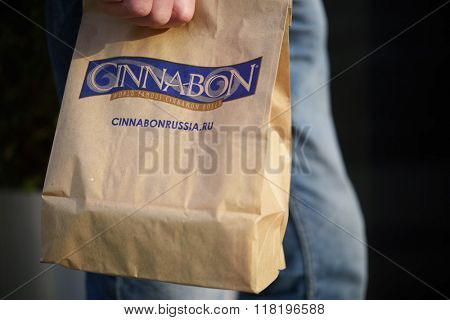 MOSCOW, RUSSIA - JULY 2, 2014: Man holding the bag with cinnamon roll from Cinnabon bakery. Forbes listed the Cinnabon as the best franchise in Russia among restaurants and cafes