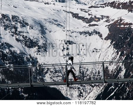 Skier walks on mountain suspension bridge
