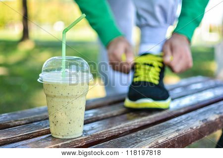 Detox smoothie drink and running footwear close up. Man athlete tying sport shoes.